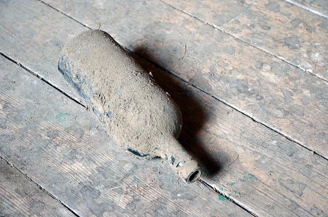 Verstaubte Glasflasche auf Boden (Bild: BRRT, CC0)
